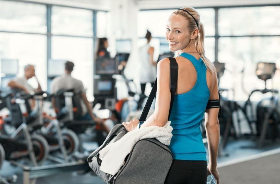 Menina chegando com mala na academia