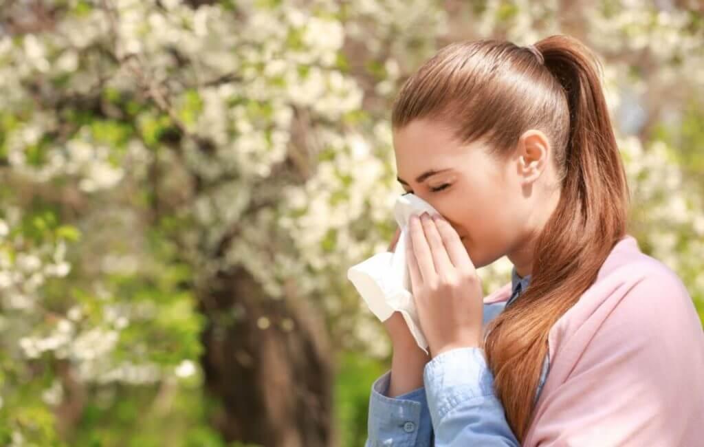 Mulher assoando o nariz em um lenço