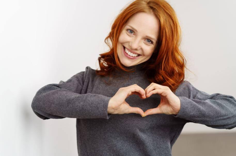 Mulher fazendo um coração com as mãos na frente do peito