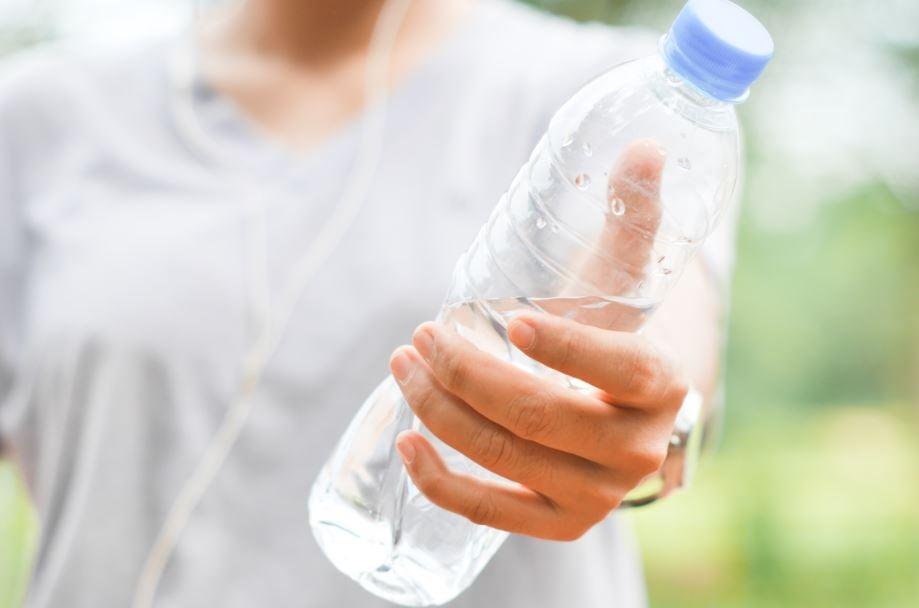 Uma mulher oferecendo uma garrafa de água