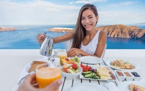 Mulher tomando café da manhã com uma vista maravilhosa de mar e montanhas