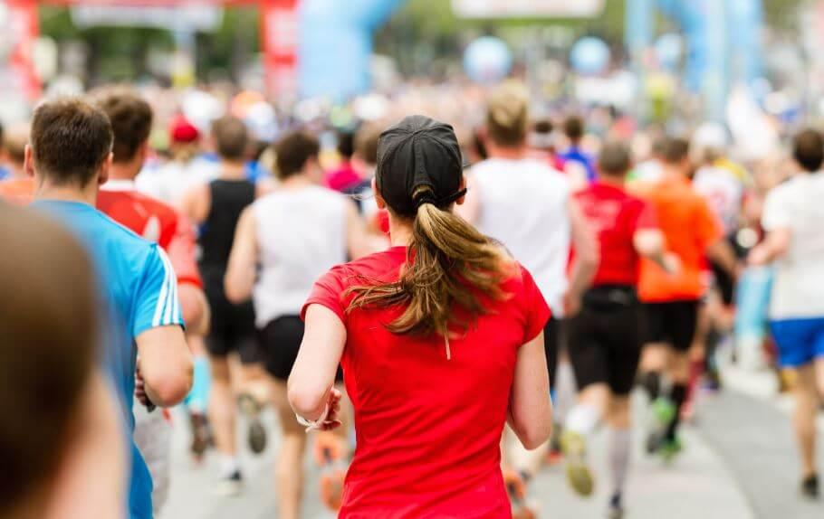 Foto tirada de trás de uma prova da maratona com as costas de uma mulher em foco
