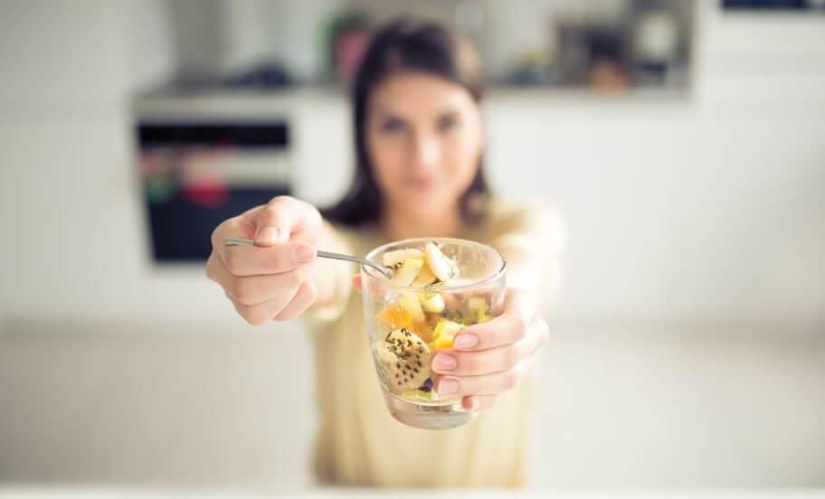 Menina comendo um pote de fruta com sementes