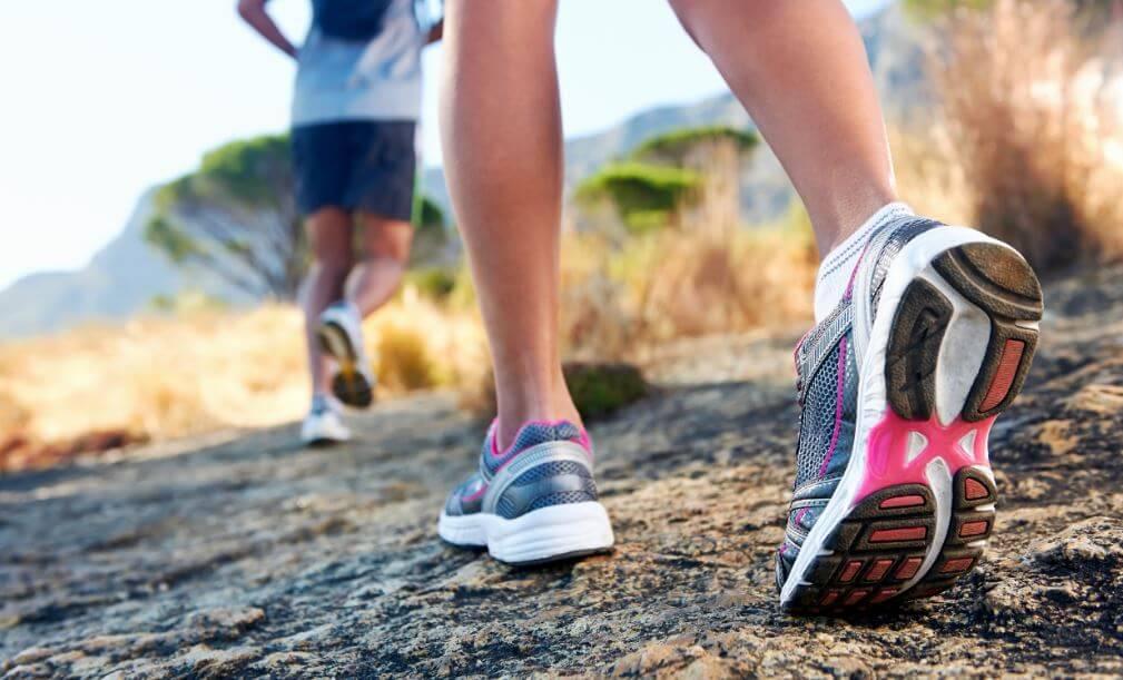 Foco nos pés de duas pessoas usando tênis de corrida nas montanhas