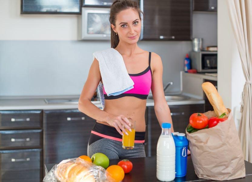Menina com roupa de academia e várias comida saudáveis