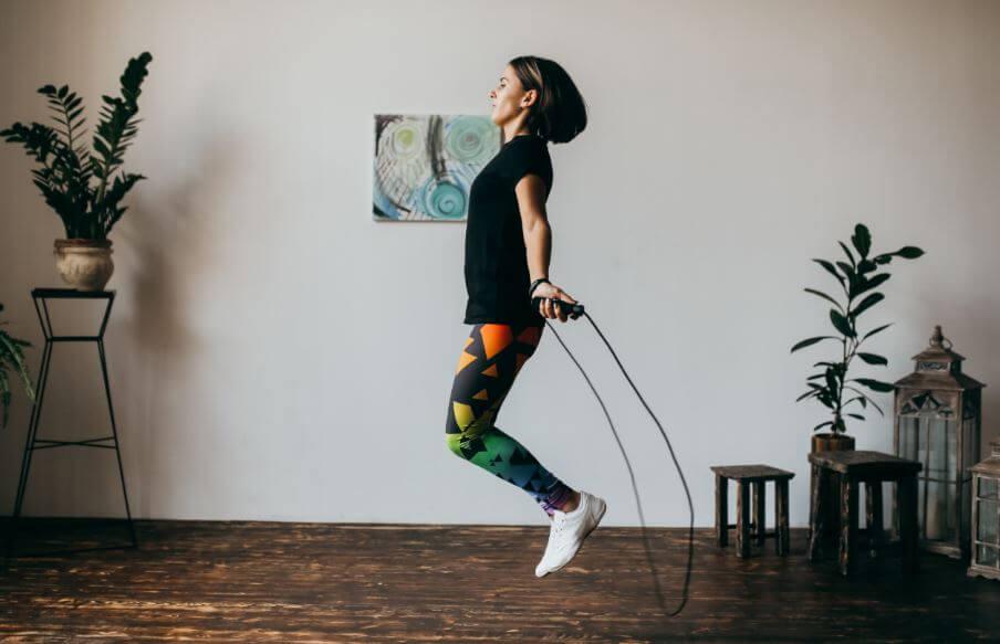 Mulher pulando corda na sala de casa