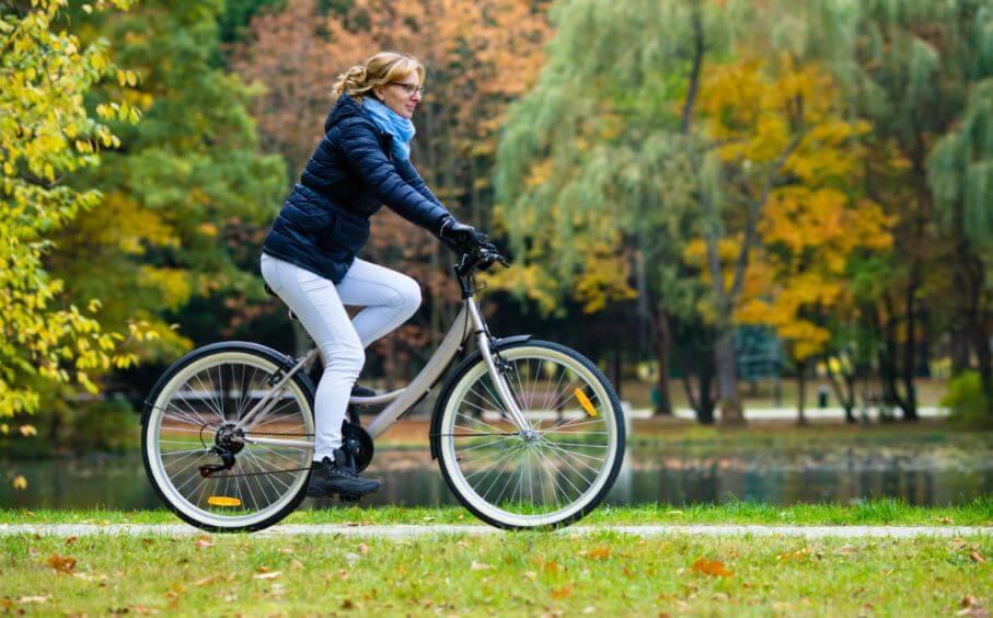 Mulher andado de bicicleta no outono e frio