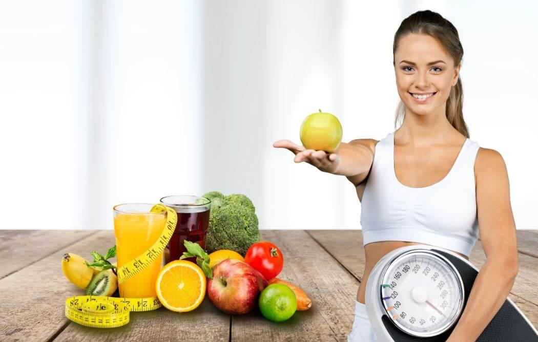 Garota oferecendo fruta diante de alimentos saudáveis com uma balança na mão
