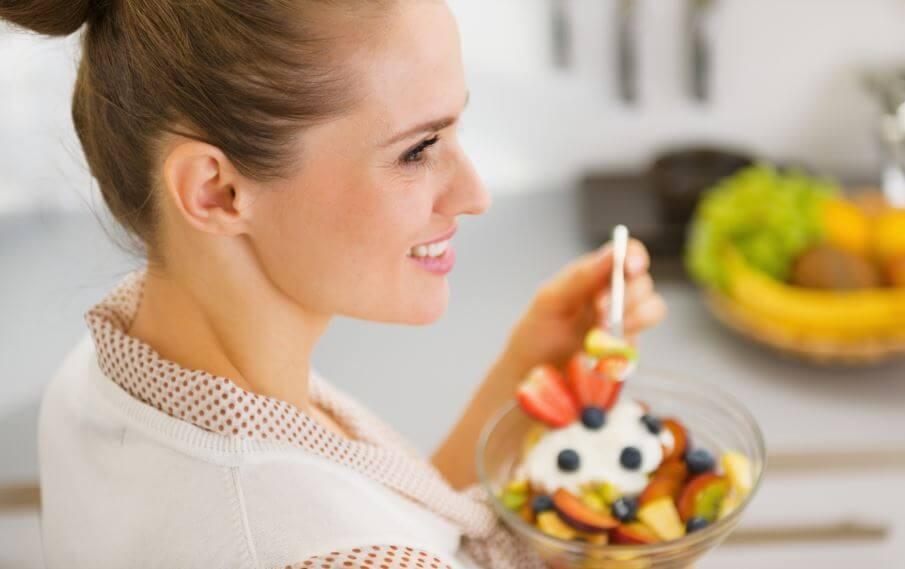 Mulher comendo yogurte com frutas