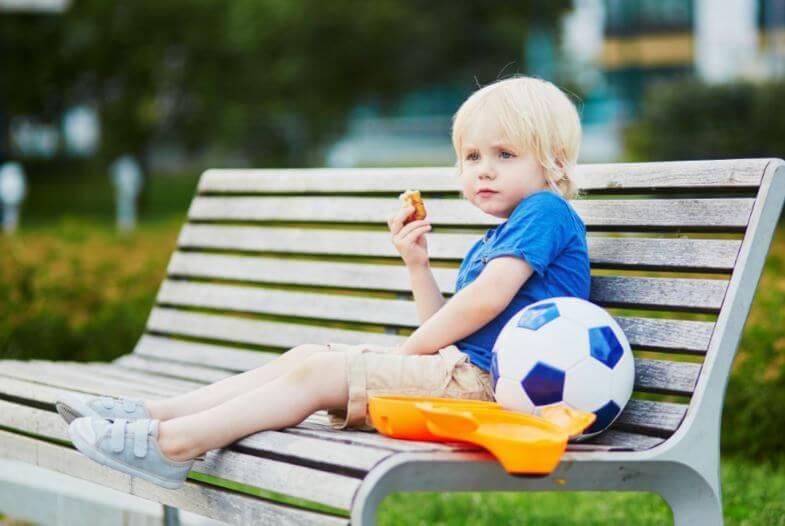 Criança comendo um lanche ao lado de uma bola de futebol