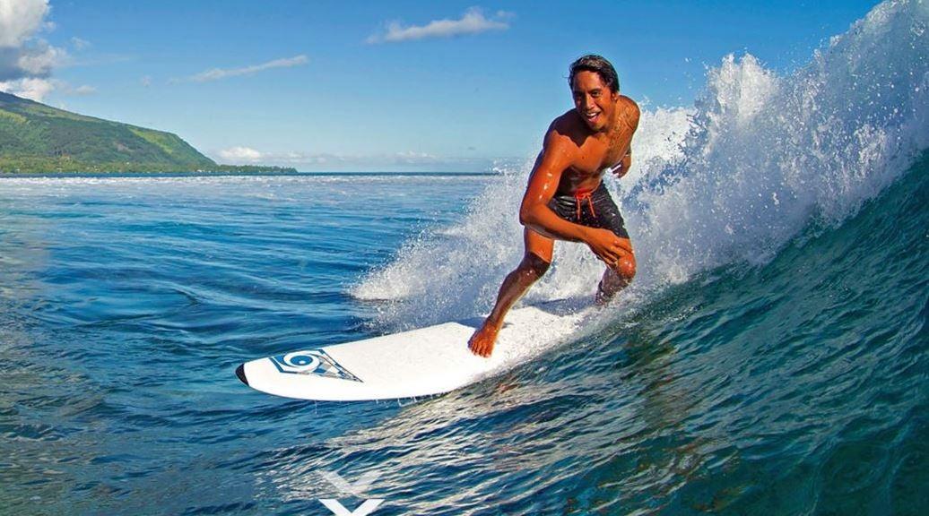 Menino surfando no mar em um dia de céu azul