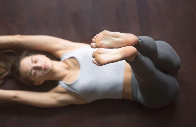 Mulher deitada no chão com as pernas para cima