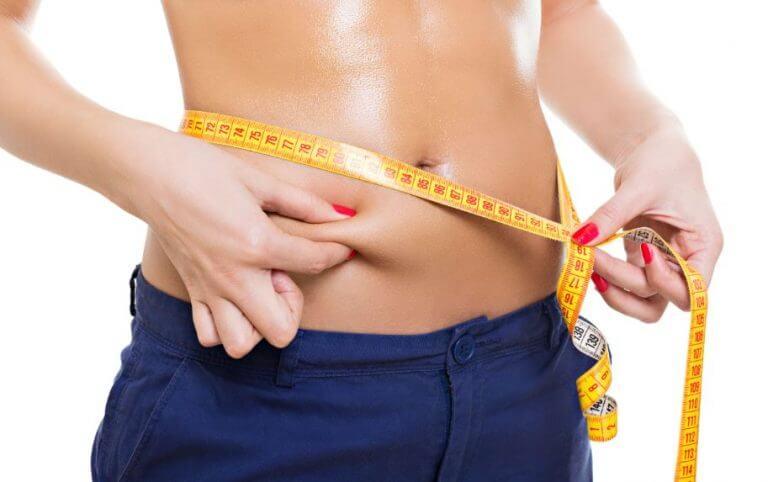 Mulher medindo a barriga com fita métrica