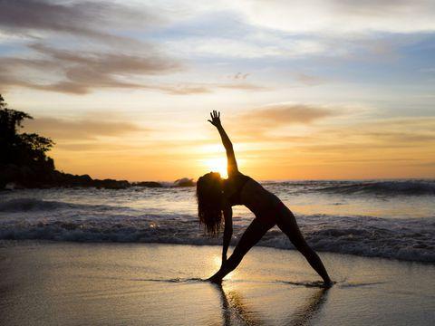 Posição de Yoga na praia
