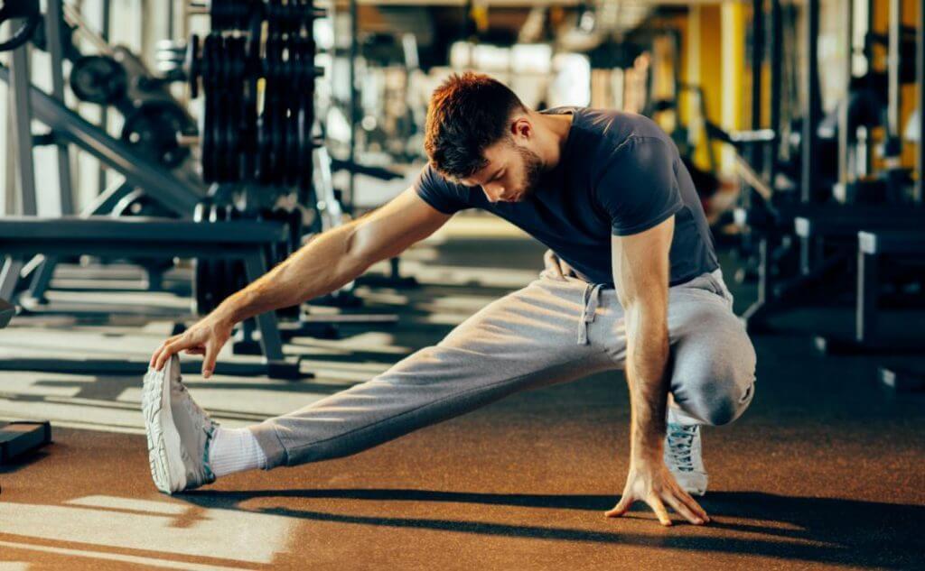 Homem se alongando para evitar lesão no CrossFit