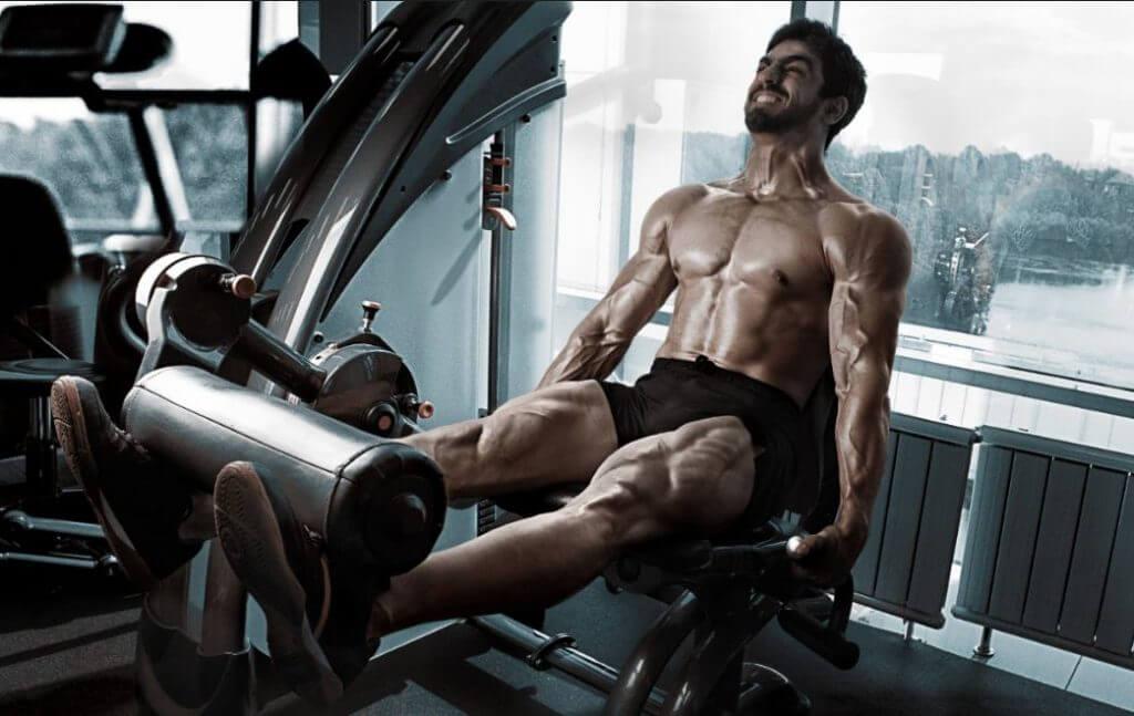 Rotina tronco perna: homem malhando perna na máquina