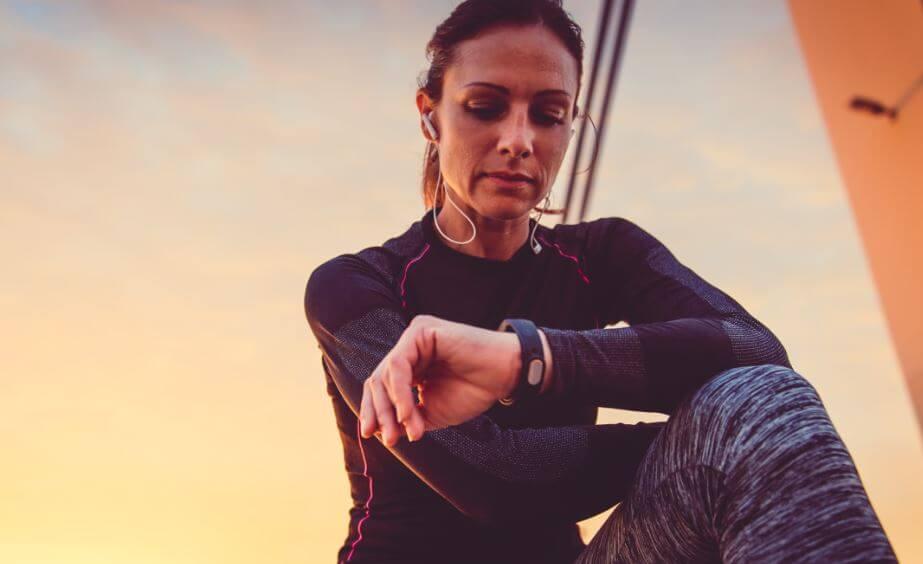 Mulher conferindo relógio ao fazer esporte