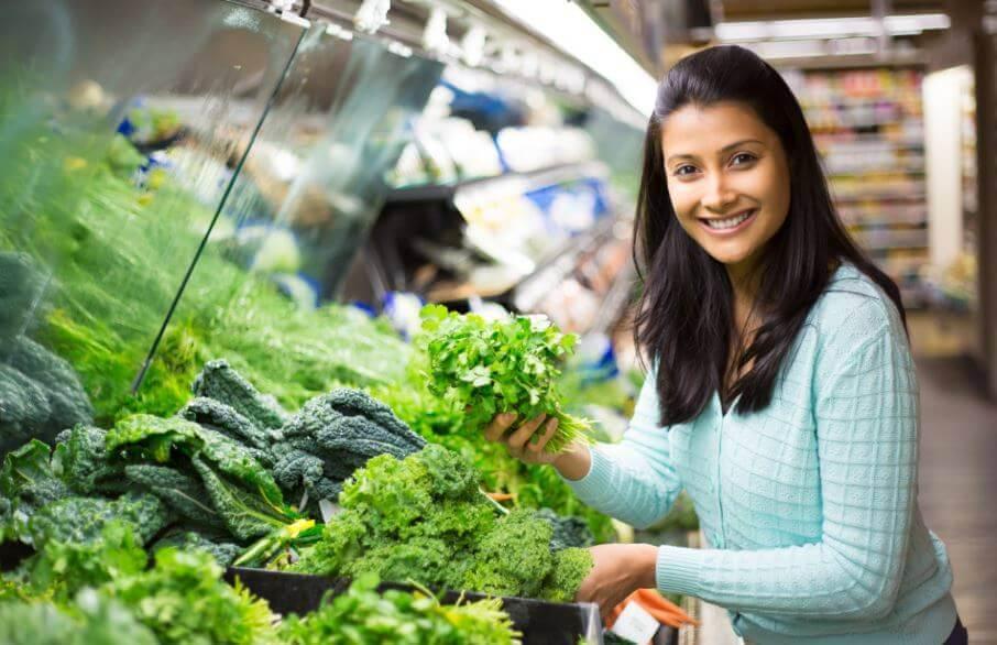 Garota fazendo compras no mercado buscando uma alimentação sustentável