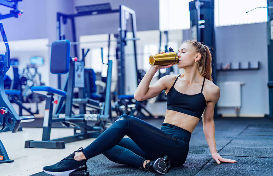 Mulher bebendo água na academia.