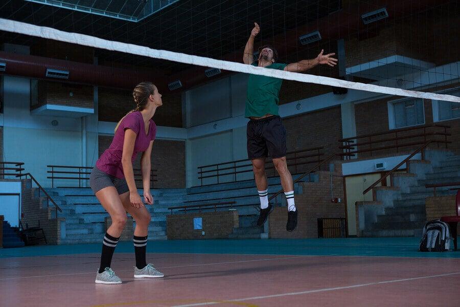 Homem saltando para sacar no vôlei