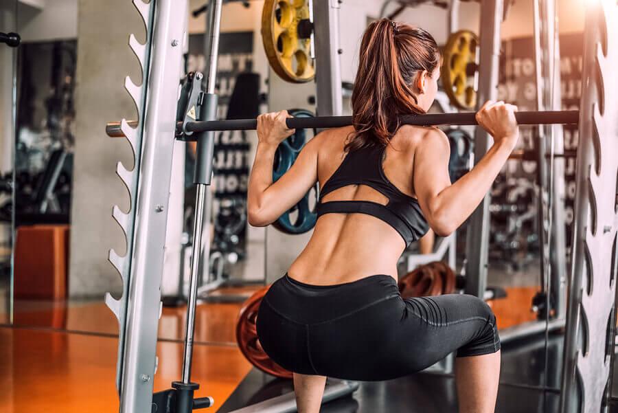 Garota fazendo exercício no smith