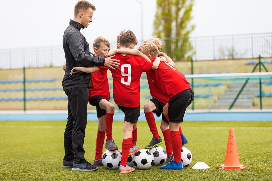 Treinador com equipe de futebol infantil