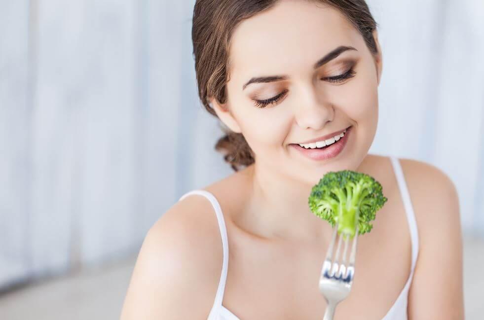 Garota comendo brócolis
