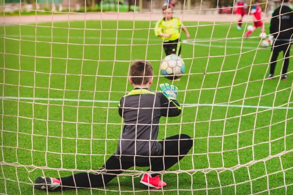 Criança cobrando penalti