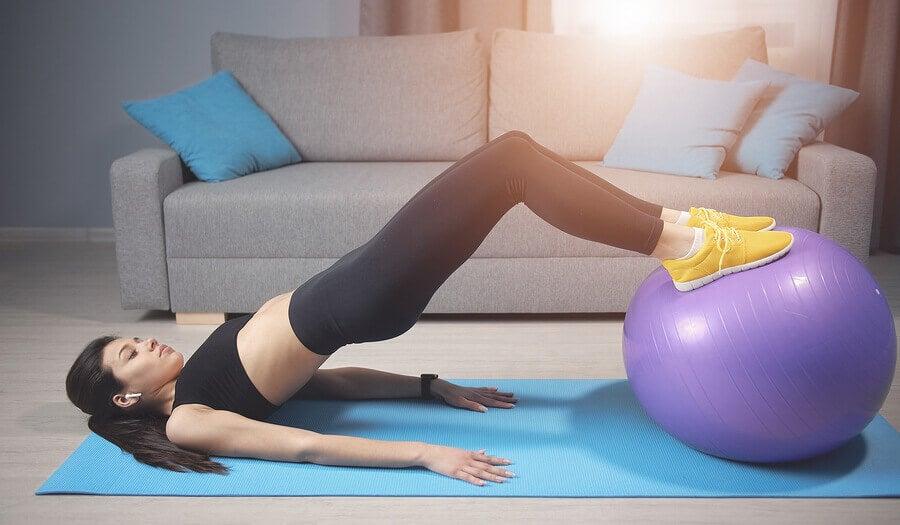 Jovem fazendo um exercício de núcleo com bola de pilates.