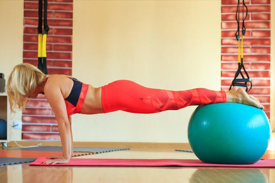 Mulher fazendo exercícios com bola de pilates em casa.