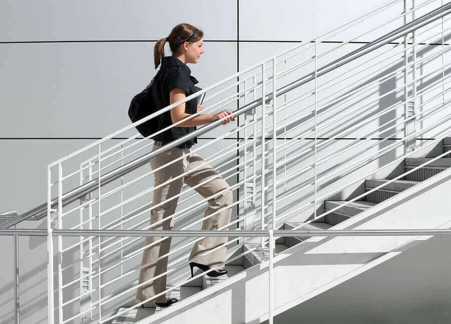 Mulher subindo escadas para melhorar a circulação nas pernas