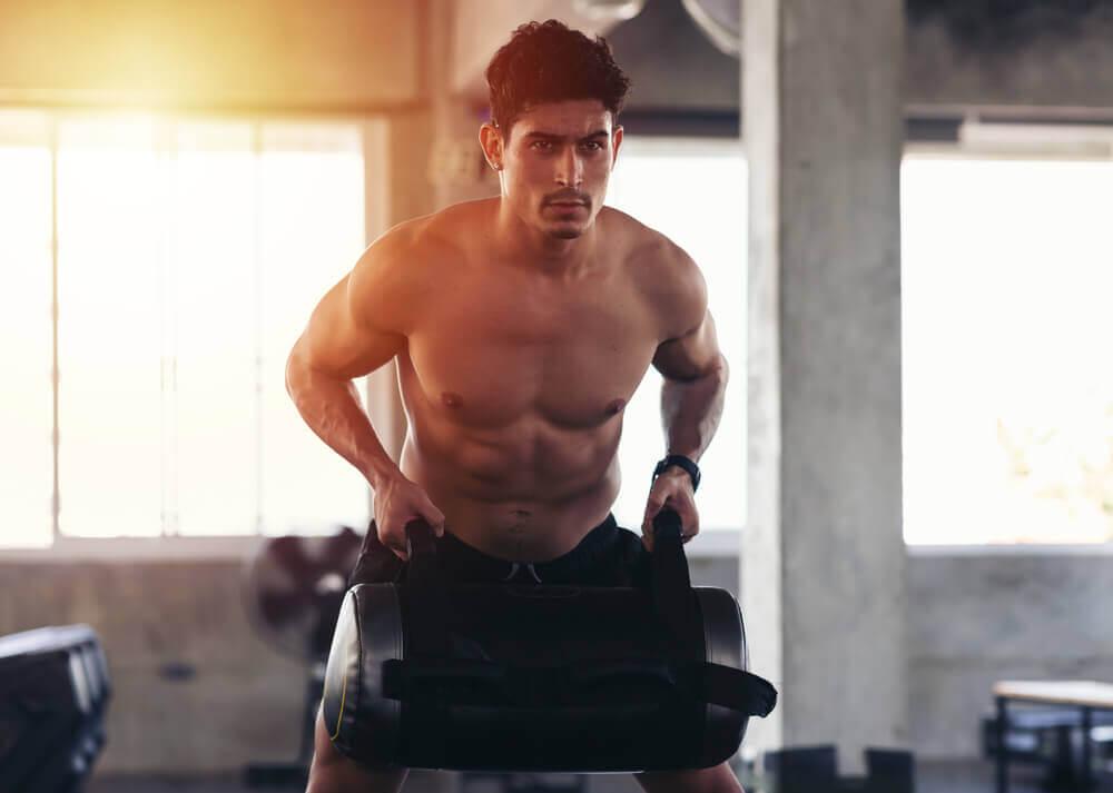 Homem fazendo remada com peso