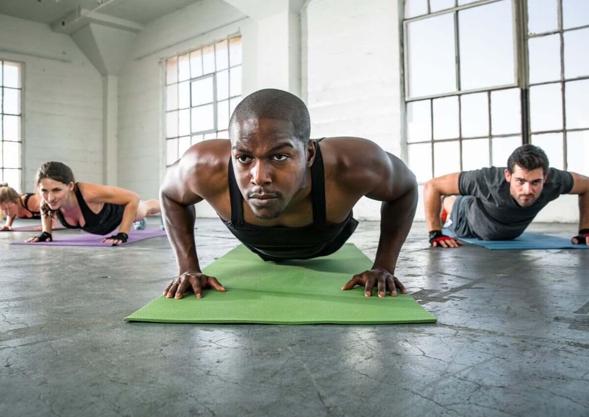 Turma fazendo flexões em aula fitness