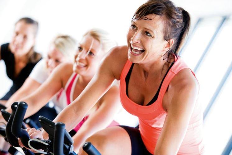 Spor salonunda kondisyon bisikletinde çalışan mutlu kadınlar.
