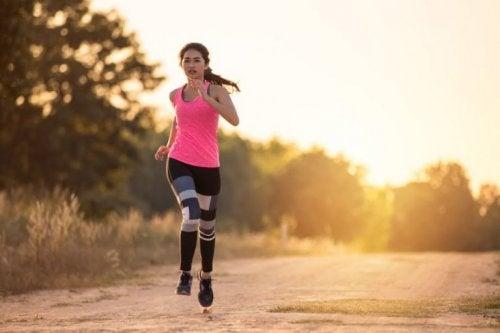 Toprak yolda koşu yapan spor kıyafetli bir kadın.