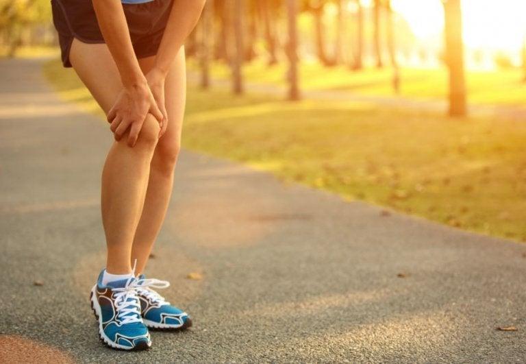 Koşarken sakatlanmış dizini tutan koşucu
