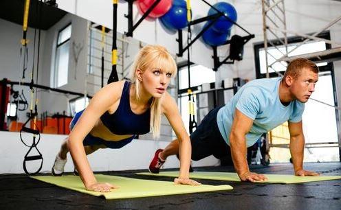 CrossFit egzersizinde şınav çeken kadın ve erkek.