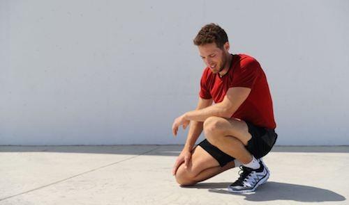 tek diz üstünde mola vermiş kırmızı tişörtlü erkek koşucu