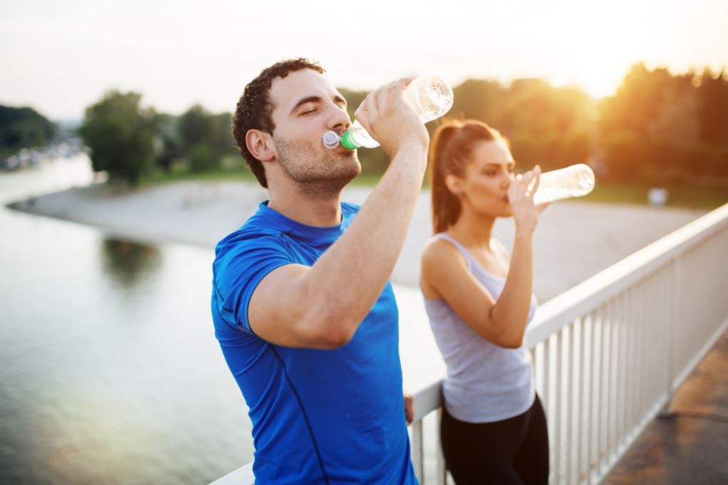Açık havada spor arasında su içen erkek ve kadın.