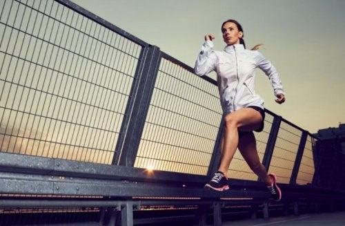 Köprü üzerinden koşu yapan spor kıyafetli bir kadın.