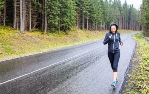 Ormanlık bir alanda, yağmurlu bir havada koşan kadın.