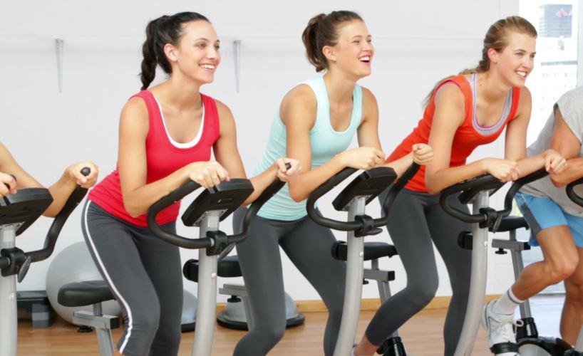 Kondisyon bisikletinde antrenman yapan kadınlar.