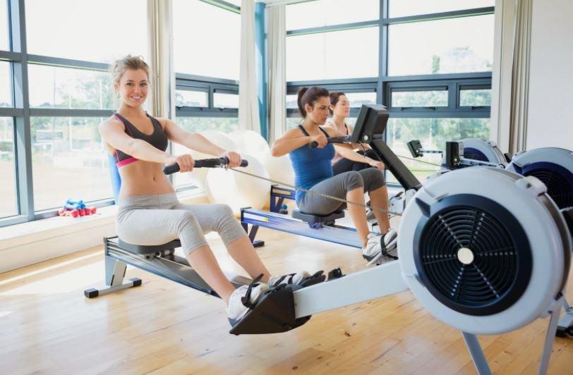 Spor salonunda kürek makinesi ile antrenman yapan kadınlar.