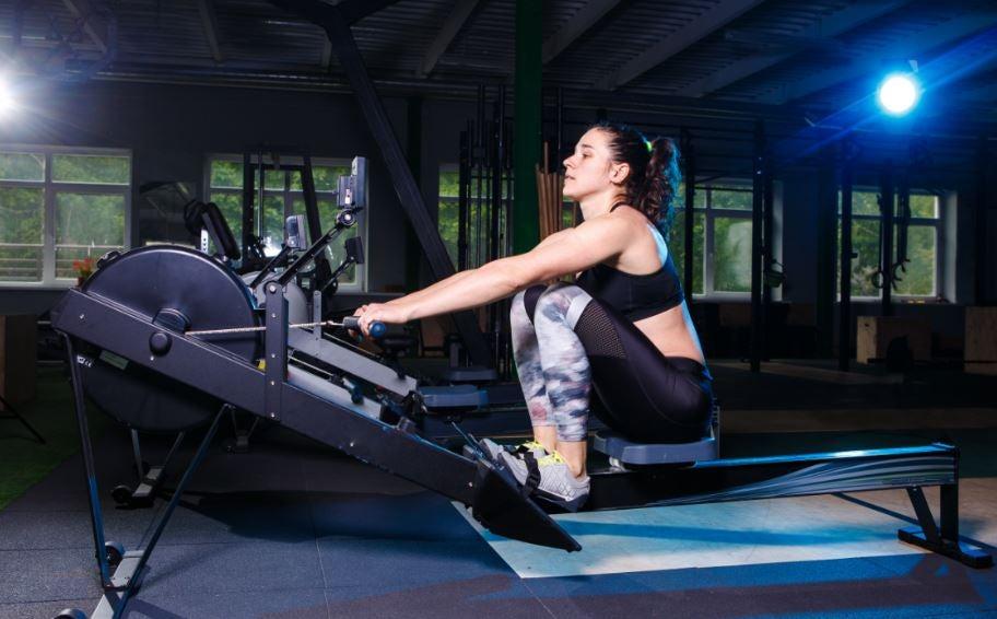 Kürek makinesi ile antrenman yapan kadın.