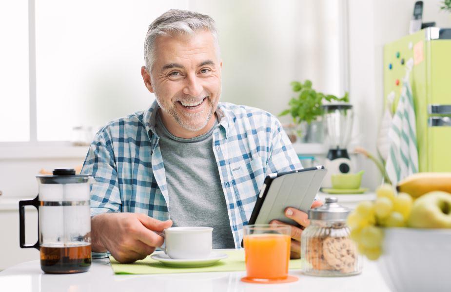 kahvaltı yapan orta yaşlı mutlu adam