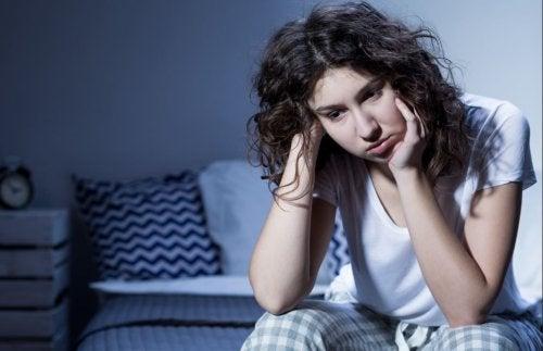 yatakta oturan düşünceli kadın