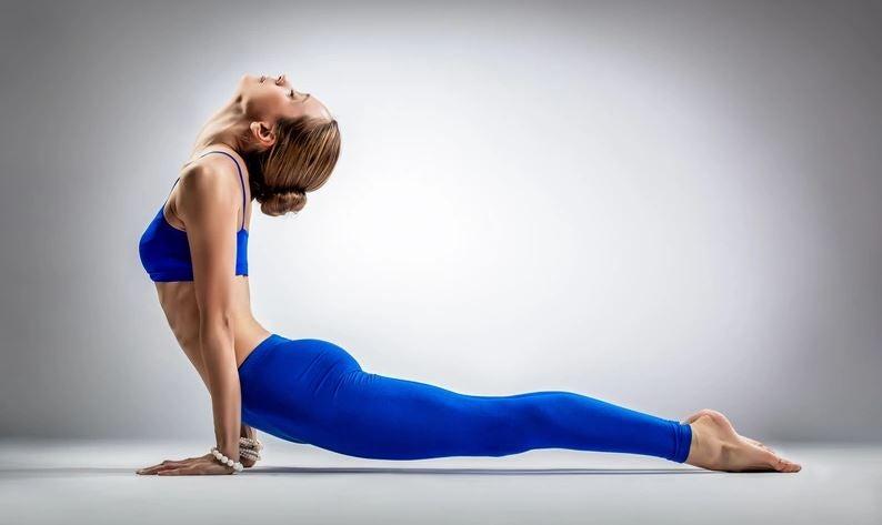 Yukarı bakan köğek yoga duruşu yapan kadın.