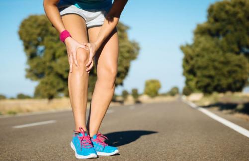 Ağrıyan dizini tutan kadın koşucu