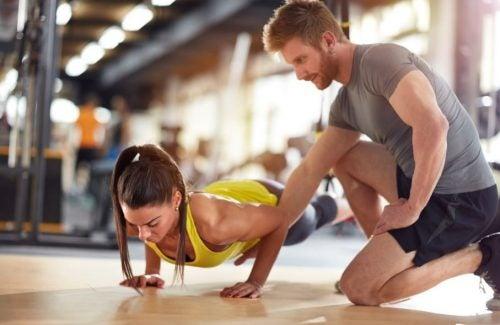 Spor eğitmeni ile şınav çeken kadın