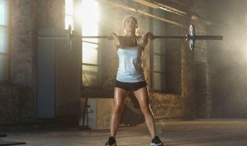 Halter ile squat egzersizi yapan bir kadın.